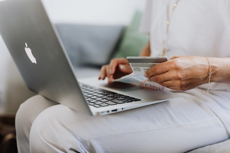 A closeup image of a woman with a mac laptop on her lap and a debit/credit card in her hands, as if she is paying for something online